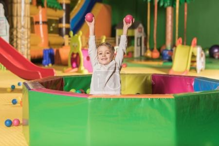Foto de Adorable niño sonriendo a la cámara jugando en la piscina con las bolas de colores - Imagen libre de derechos