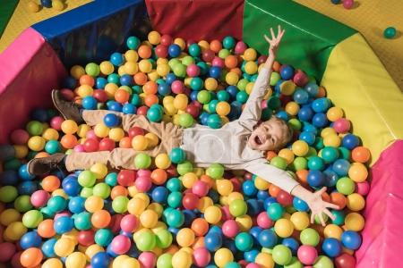 Photo for High angle view of happy little boy lying in pool with colorful balls - Royalty Free Image