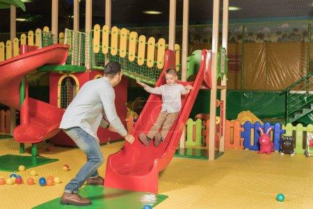 Photo pour Père avec adorable petit fils jouant sur la glissière au centre de jeu intérieur - image libre de droit