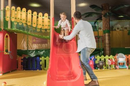 Photo pour Vue arrière du père regardant le petit fils jouant sur la glissière dans le centre de divertissement - image libre de droit