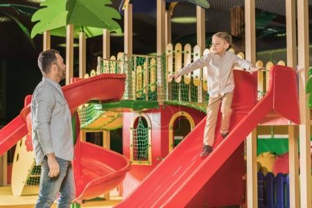 Foto de Padre mira hijito lindo jugar en diapositiva en el centro de entretenimiento - Imagen libre de derechos