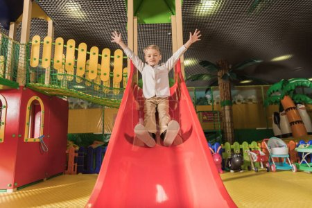 cute happy little boy with raised hands playing on slide in entertainment center