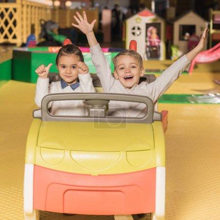 Foto de Adorables hermanos felizes sentado en el coche de juguete y sonriendo a la cámara en el centro de entretenimiento - Imagen libre de derechos