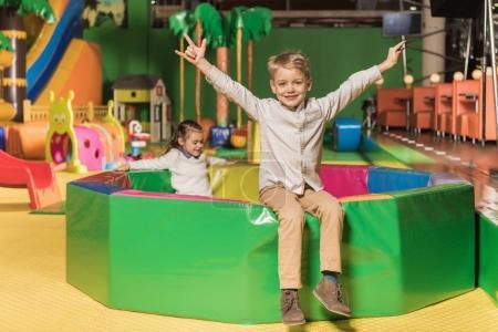 Foto de Lindo niño sonriendo a cámara mientras hermana jugando en la piscina con las bolas de colores en el centro de juego - Imagen libre de derechos