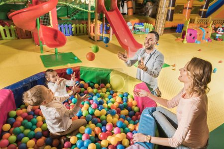 Photo for Happy parents with adorable little kids playing with colorful balls in entertainment center - Royalty Free Image