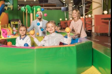 Foto de Padres felices mirando niños lindos sonriendo a cámara y jugar con las bolas de colores en el centro de juego - Imagen libre de derechos