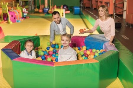 Foto de Felices padres mirar lindo poco a los niños sonriendo a la cámara mientras está sentado en la piscina con las bolas de colores - Imagen libre de derechos