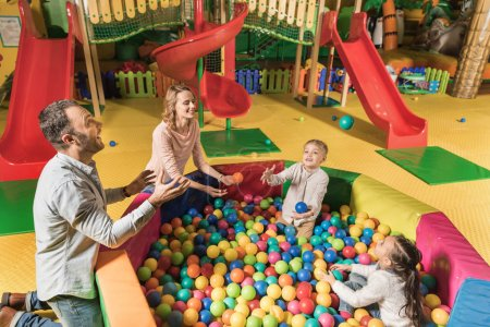 high angle view of happy family playing with colorful balls in entertainment center