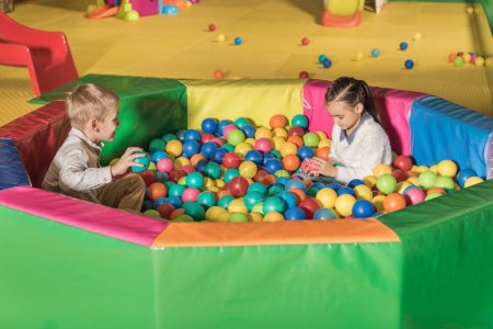 cute little kids playing in pool with colorful balls