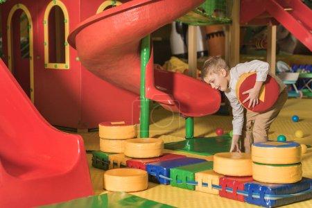 mignon petit garçon heureux jouant avec des blocs dans le centre de jeu