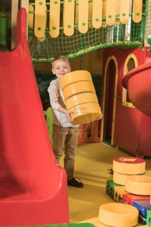 happy little boy smiling at camera while playing with blocks in entertainment center