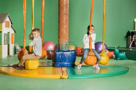 adorable smiling siblings swinging and playing in entertainment center