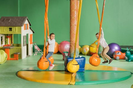 happy little children swinging and playing in entertainment center