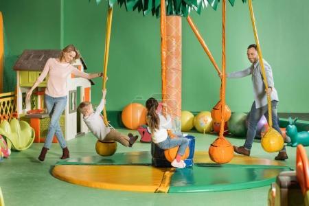 Foto de Padres sonrientes mirando niños felices en columpios en centro de entretenimiento - Imagen libre de derechos