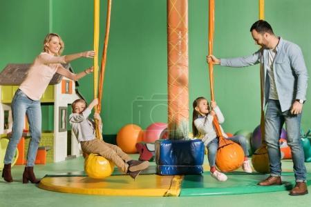Foto de Padres felices mirando a los niños en columpios en centro de entretenimiento - Imagen libre de derechos