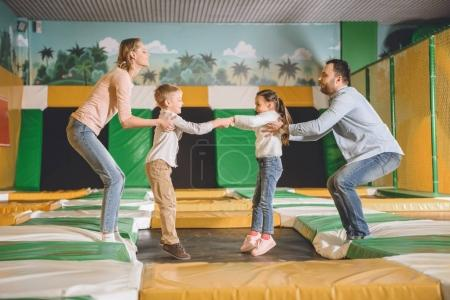 side view of happy family with two kids playing together in game center