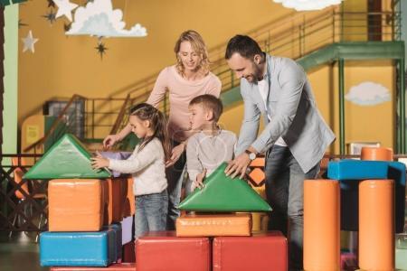 Foto de Felices padres con niños pequeños adorables jugando con bloques de colores en el centro de juego - Imagen libre de derechos