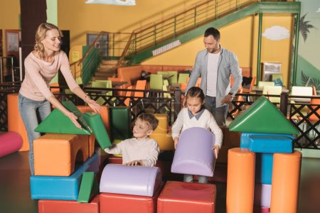 happy family with two kids playing with colorful blocks in game center