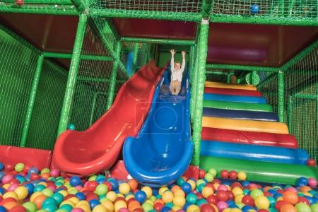 happy little boy sliding in pool with colorful balls