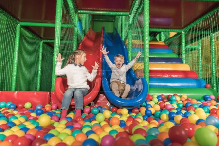 Photo for Adorable happy little kids sliding in pool with colorful balls - Royalty Free Image