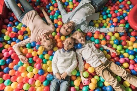 Photo pour Vue de dessus d'une famille heureuse avec deux enfants, souriant à la caméra en position couchée dans la piscine avec des boules colorées - image libre de droit