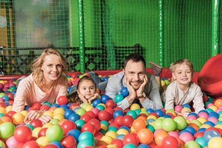happy family with two kids smiling at camera while lying in pool with colorful balls