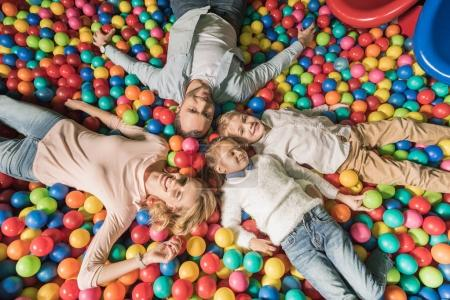 Photo for Top view of happy family smiling at camera while lying in pool with colorful balls - Royalty Free Image