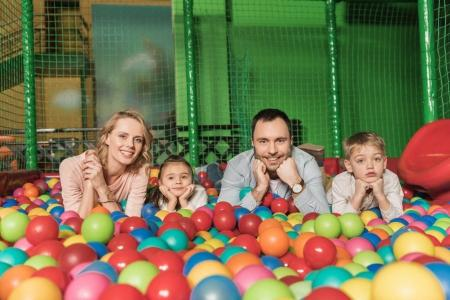 happy family smiling at camera while lying in pool with colorful balls
