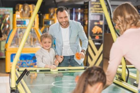 Photo pour Heureuse famille avec deux enfants hockey d'air jouant ensemble dans un centre de divertissement - image libre de droit