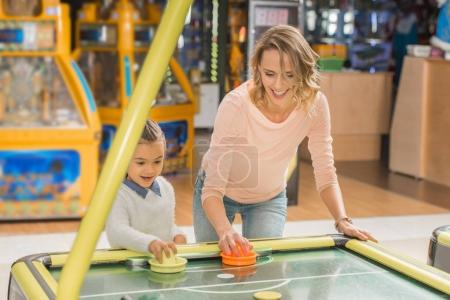 Photo for Happy mother and daughter playing air hockey together in entertainment center - Royalty Free Image