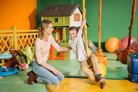 happy mother looking at cute smiling son swinging in entertainment center