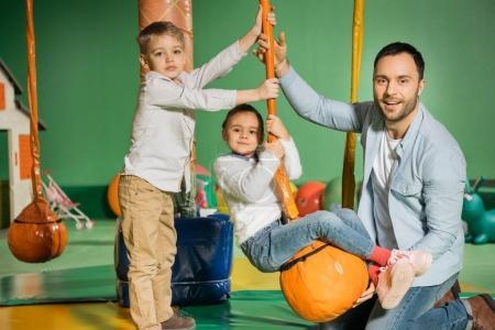 Foto de Padre feliz con niños adorables sonriendo a cámara mientras jugaba en el centro de entretenimiento - Imagen libre de derechos