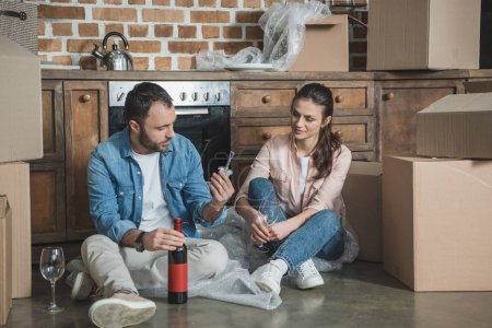 young couple opening bottle of wine while celebrating relocation in new house
