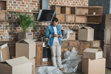 man using smartphone while standing between cardboard boxes in new apartment