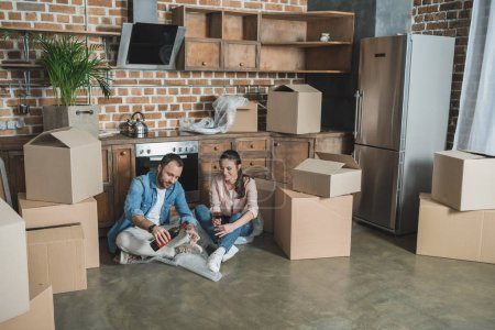 happy young couple drinking wine in new apartment