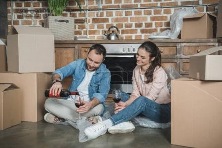Photo for Happy young couple drinking wine and celebrating relocation in new house - Royalty Free Image