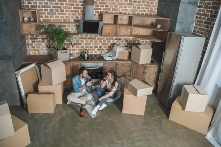 high angle view of happy young couple drinking wine and celebrating relocation in new house