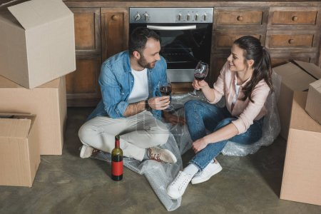 high angle view of happy young couple drinking wine and celebrating relocation