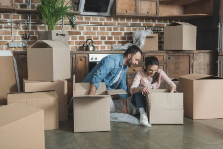 Photo for Smiling young couple unpacking boxes while moving in new house - Royalty Free Image