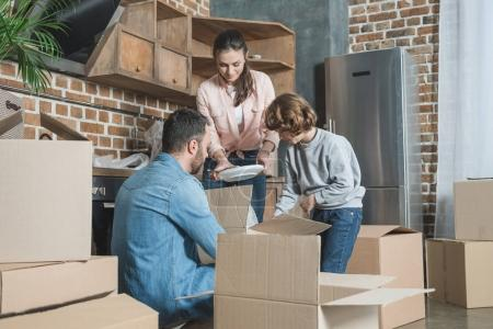Photo for Happy family unpacking cardboard boxes in new house - Royalty Free Image