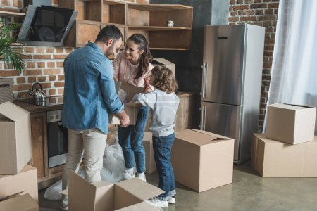 Photo for Happy family packing cardboard boxes while moving home - Royalty Free Image