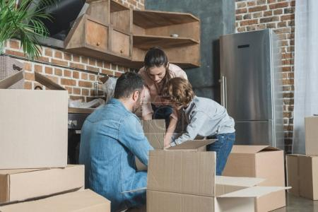 Photo for Family with one child unpacking cardboard boxes in new apartment - Royalty Free Image
