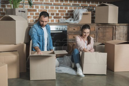 happy young couple packing cardboard boxes during relocation