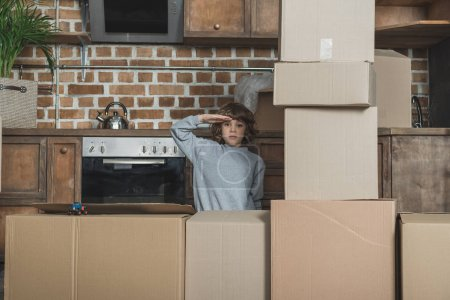 little boy saluting and looking at camera while playing with cardboard boxes in new apartment