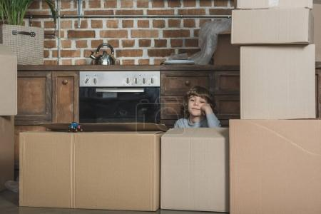 cute little boy looking at camera while playing with cardboard boxes in new house