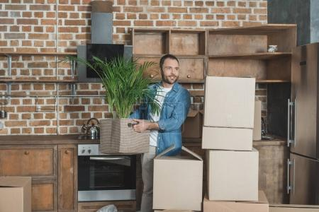 smiling man holding potted plant while moving in new apartment