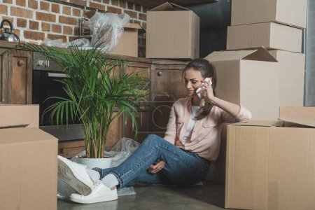 smiling young woman talking by smartphone while sitting between cardboard boxes in new apartment
