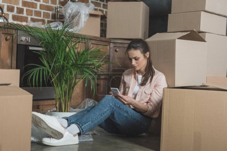 Photo for Young woman using smartphone while sitting between cardboard boxes in new apartment - Royalty Free Image
