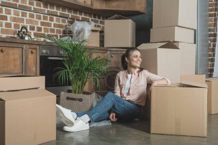 happy young woman smiling and looking away while sitting with cardboard boxes in new apartment