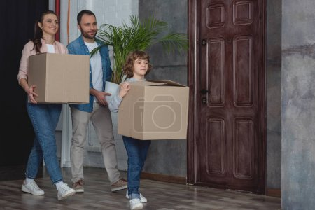 Photo for Happy family with cardboard boxes and potted plant moving home - Royalty Free Image